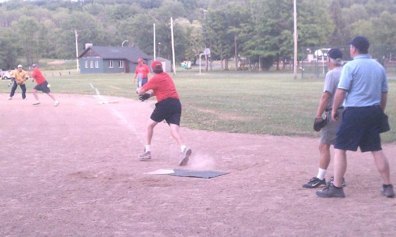 Wilson Curry of the DUDAS hits a blast towards runner Tony DiFillipo and 1st bas